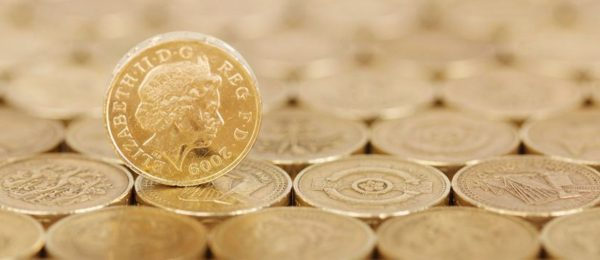 Pound coins adjoining each other on a flat surface with a singular coin stood atop